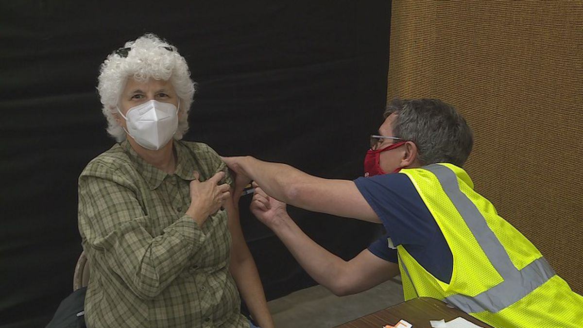 A woman receives a dosage of the COVID-19 vaccine at Agriculture Hall at a vaccine clinic.
