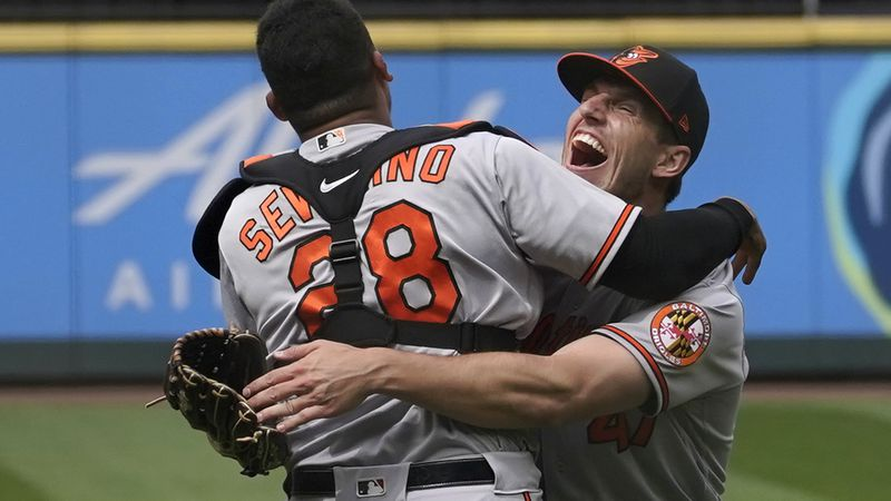 Baltimore Orioles starting pitcher John Means, right, hugs catcher Pedro Severino after Means...