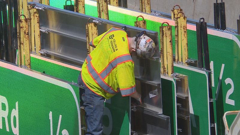 Workers put up new signage along I-70 on April 29.