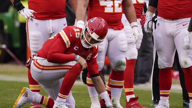 Kansas City Chiefs quarterback Patrick Mahomes kneels on the field after getting injured during...
