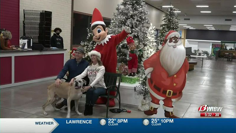 A dog and his owners take a photo with the Topeka Christmas Elf at Fairlawn Plaza Mall on...