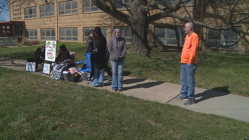 A group gathers outside the Kansas Department of Labor on Wednesday, March 31, 2021 for an...