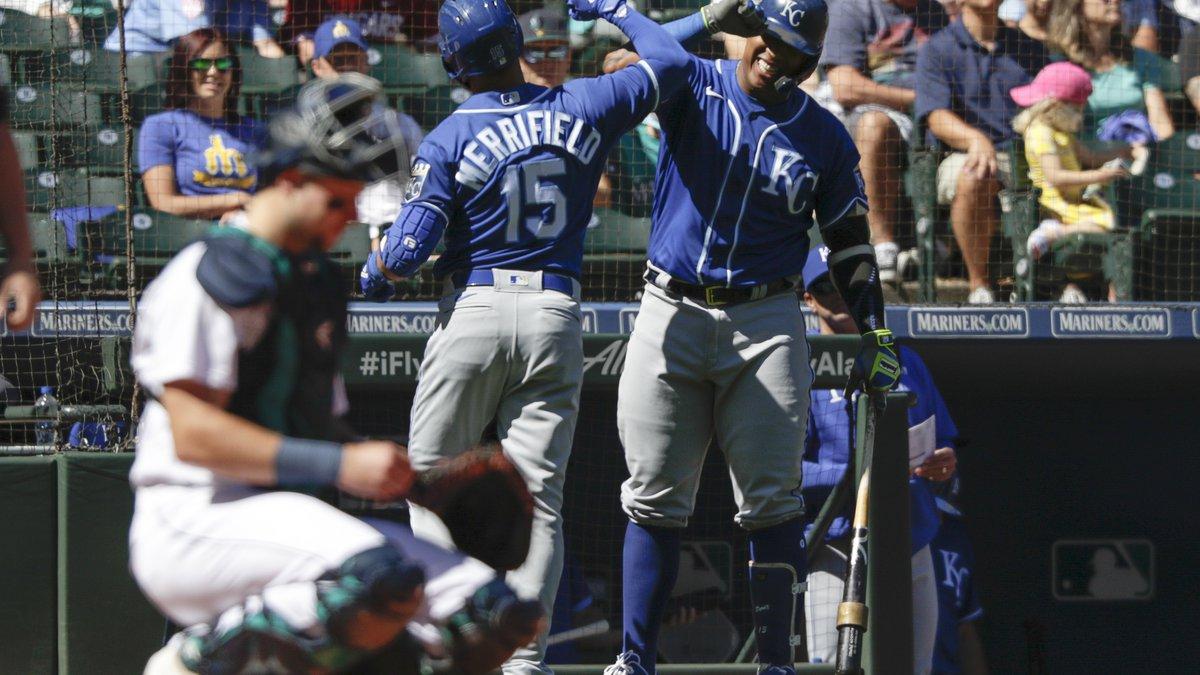 Kansas City Royals' Whit Merrifield celebrates with teammate Salvador Perez after Merrifield's...