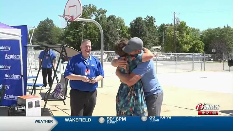 Riley County Grade School first grade teacher, Janeil Sullivan, hugs Riley County alumnus,...