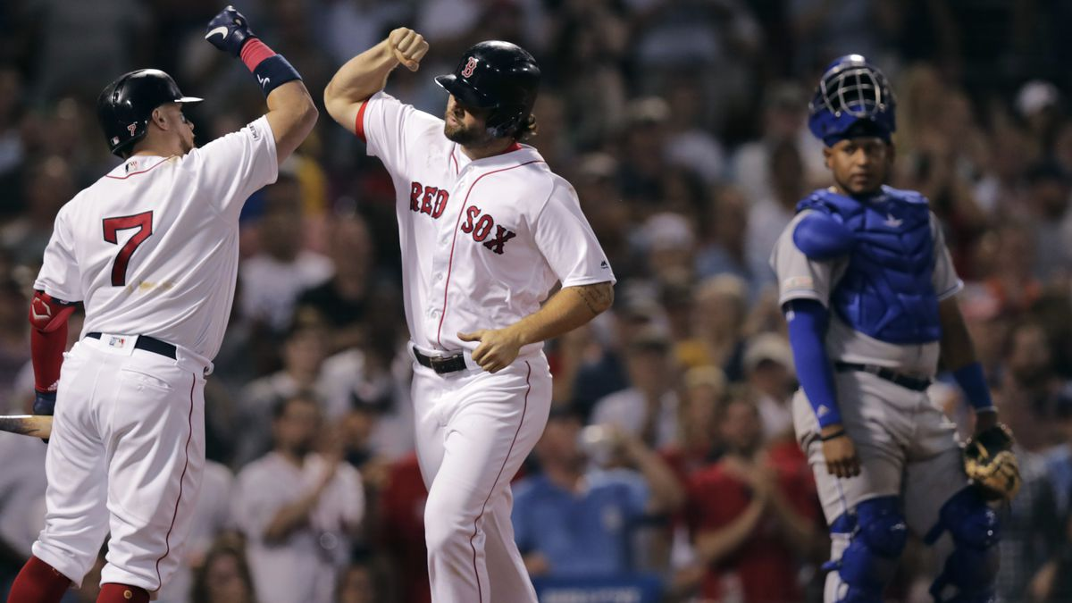 Boston Red Sox's Sam Travis, center, is congratulated by Christian Vazquez (7) after his two run home run off Kansas City Royals pitcher Mike Montgomery during the third inning of a baseball game at Fenway Park in Boston, Monday, Aug. 5, 2019. At right is Kansas City Royals catcher Meibrys Viloria.(AP Photo/Charles Krupa)