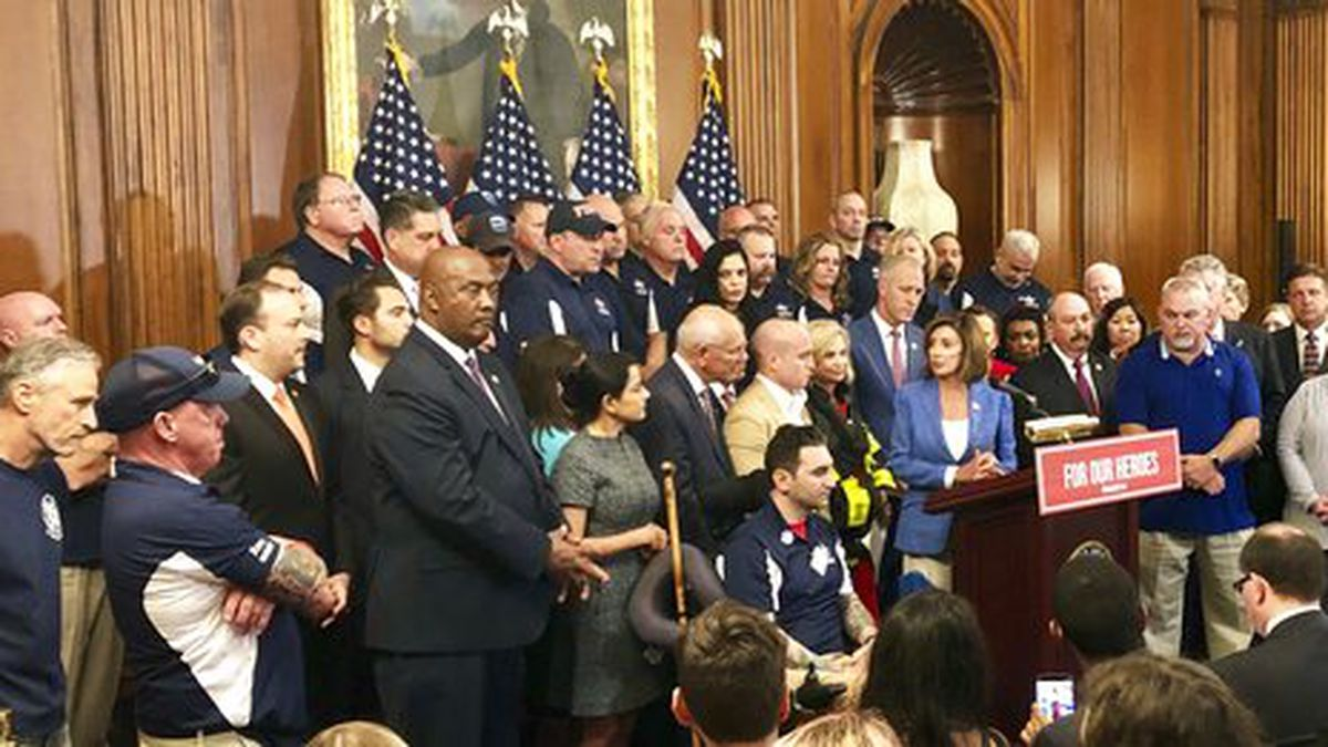 House Speaker Nancy Pelosi speaks at a news conference on behalf of 9/11 victims and families, Friday, July 12, 2019, at the Capitol in Washington. The House is expected to approve a bill Friday ensuring that a victims' compensation fund for the Sept. 11 attacks never runs out of money. Entertainer and activist Jon Stewart, listens at left. (AP Photo/Matthew Daly)