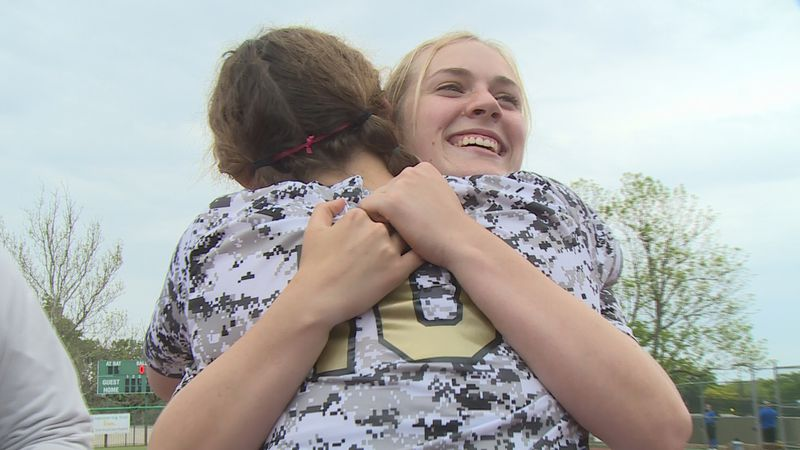 Topeka High senior catcher Zoe Caryl hugs her teammate after the Trojans won their first...