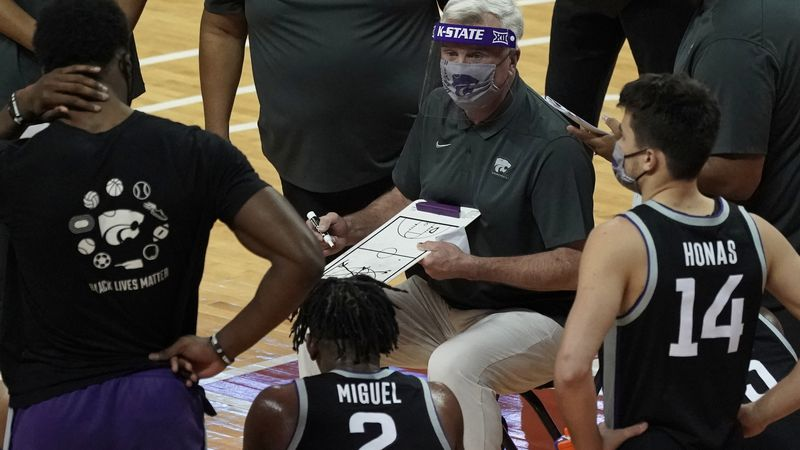 Kansas State head coach Bruce Weber, center, directs his team during a timeout during the first...