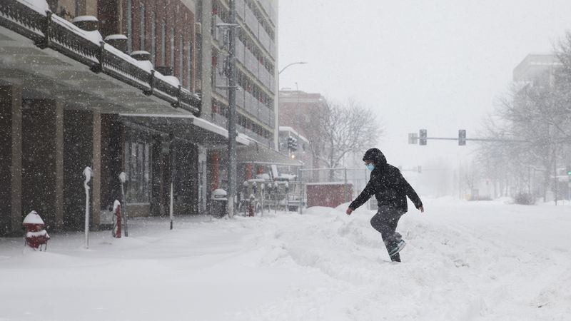 A pedestrian steps in tire tracks while crossing the street during a winter storm in downtown...