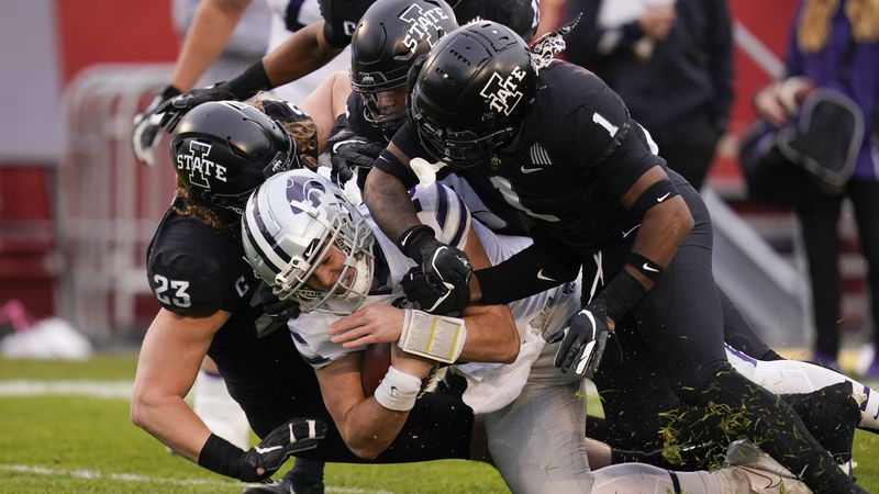 Kansas State quarterback Will Howard, center, is tackled by Iowa State defenders Mike Rose (23)...