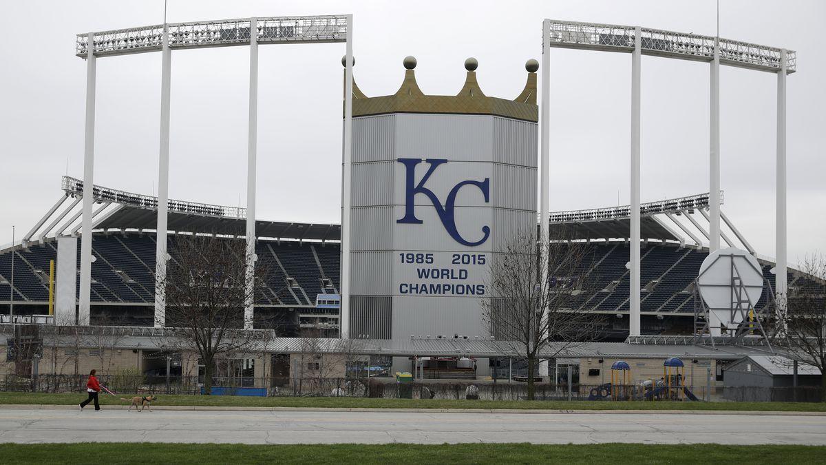 A woman and her dog walk past Kauffman Stadium, home of the Kansas City Royals baseball team,...