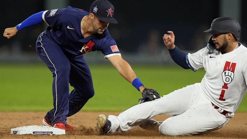 American League's Whit Merrifield, of the Kansas City Royals, tags out National League's Omar...