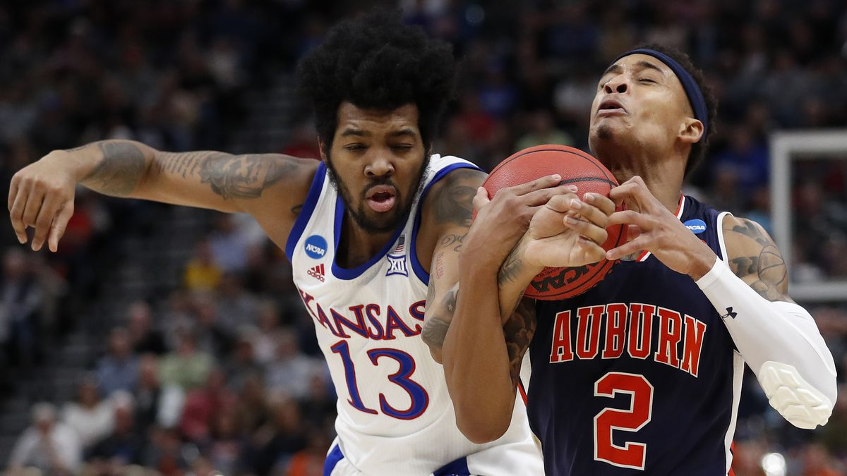 Kansas guard K.J. Lawson (13) reaches in for the ball on Auburn guard Bryce Brown (2) during the first half of a second-round game in the NCAA men's college basketball tournament Saturday, March 23, 2019, in Salt Lake City. (AP Photo/Jeff Swinger)