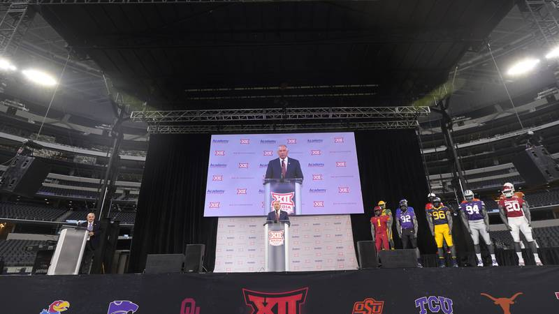 Big 12 commissioner Bob Bowlsby, center, speaks during NCAA college football Big 12 media days...