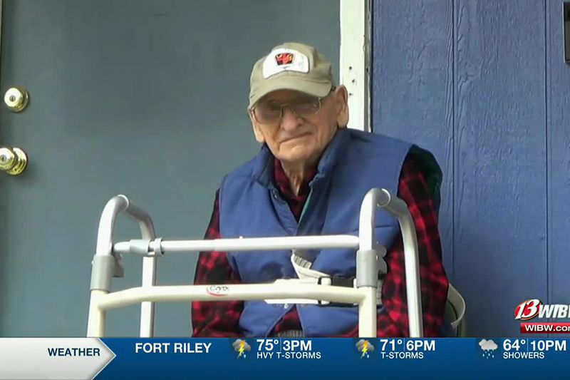 Carrol Joy, a World War II veteran watches a drive-by birthday party for him on Saturday, May...