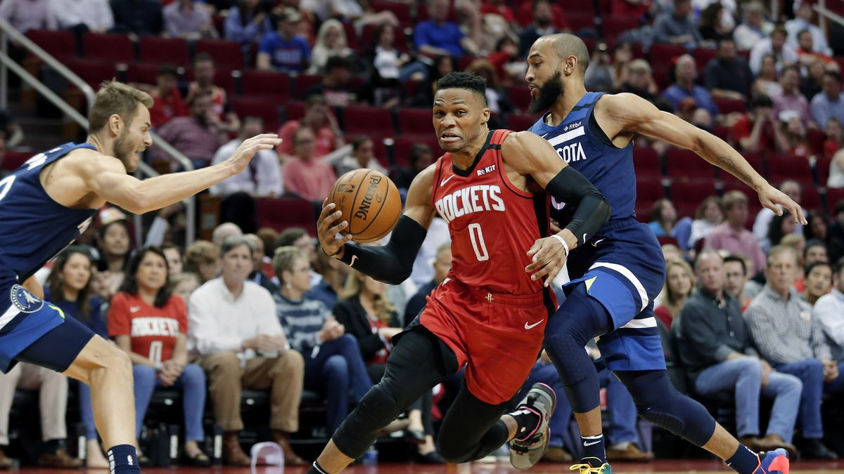 Houston Rockets guard Russell Westbrook (0) drives between Minnesota Timberwolves guards Jake Layman, left, and Jordan McLaughlin during the second half of an NBA basketball game Tuesday, March 10, 2020, in Houston.