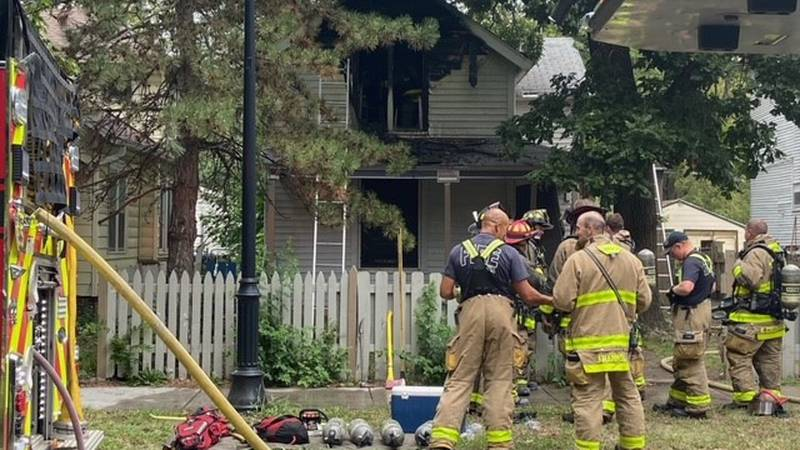Fire crews stand outside a home at 1278 SW Lane after a fire broke out inside Tuesday afternoon.