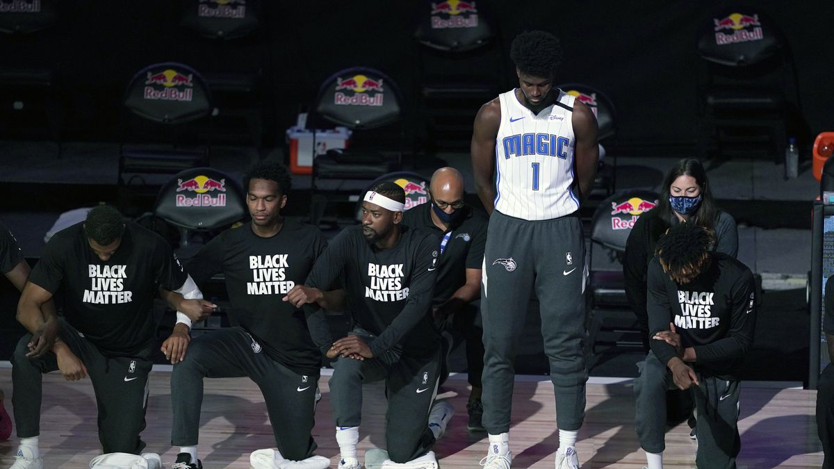 Orlando Magic's Jonathan Isaac (1) stands as others kneel before the start of an NBA basketball...