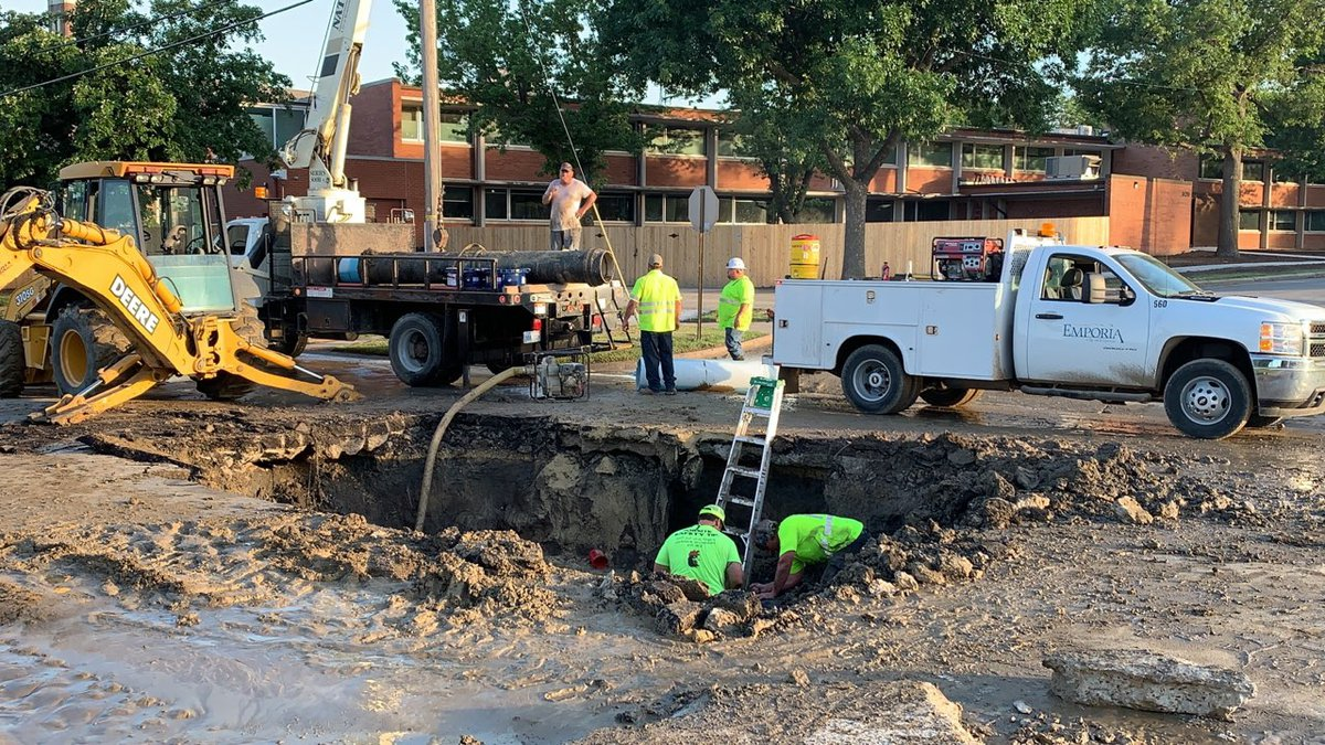 Crews work in a large crater created by a 16-inch water main line break along 12th Street in...