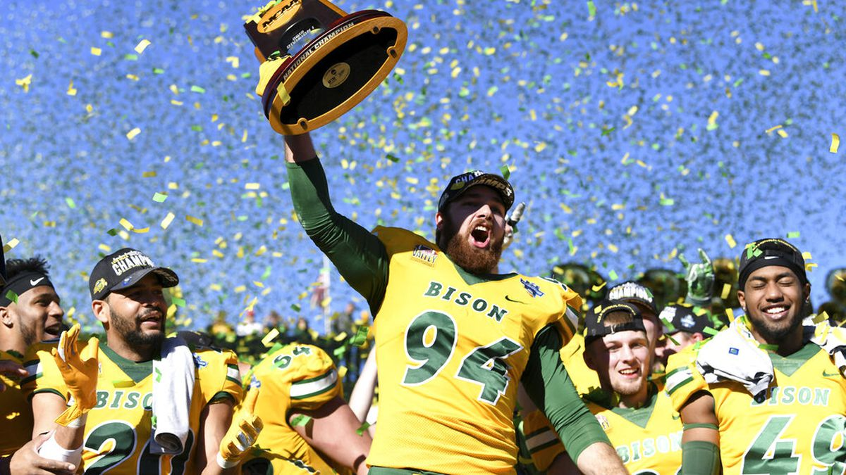 In this Jan. 5, 2019 file photo, North Dakota State defensive end Stanley Jones (94) hoists the trophy after beating Eastern Washington in the FCS Football Championship NCAA college football game, in Frisco, Texas. The NCAA Division I Council has proposed a framework to conduct a season in the Football Championship Subdivision, with teams limited to eight regular-season games in the spring and a playoff bracket reduced from 24 to 16 teams.
