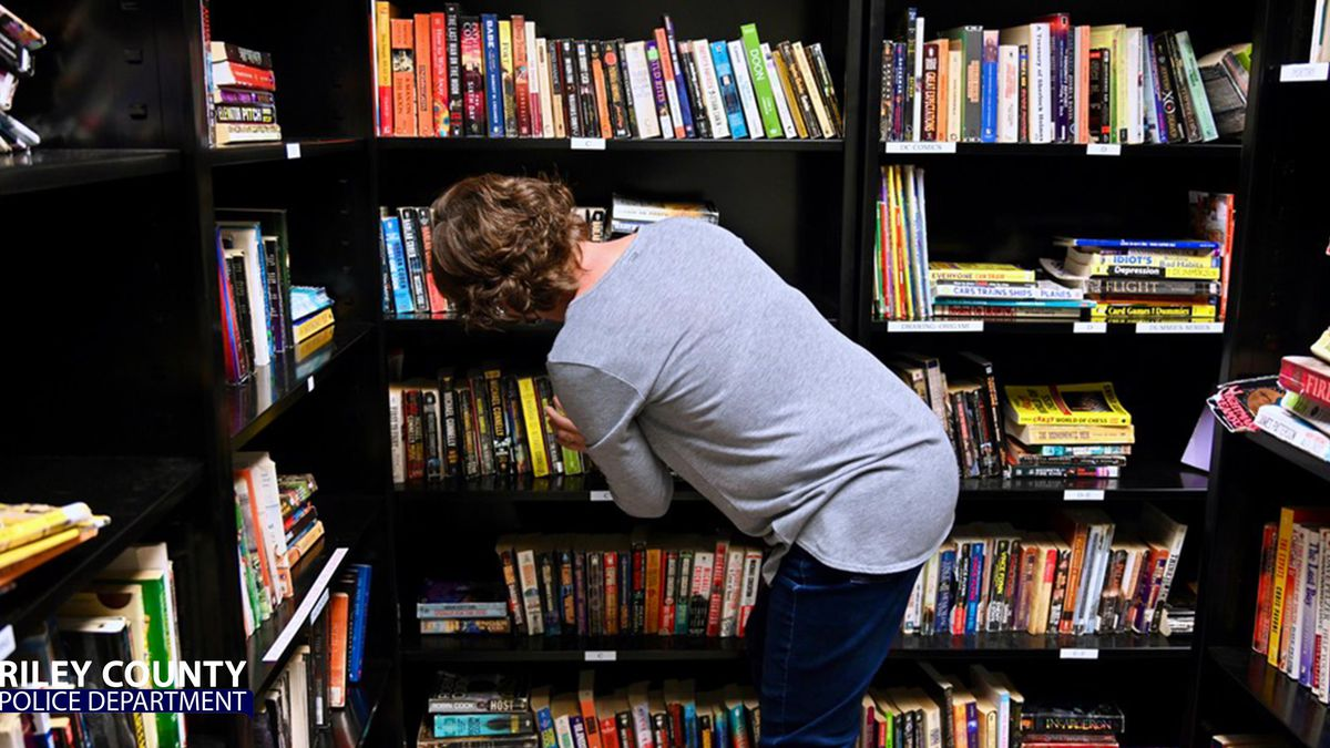 Riley Co. Jail Volunteer Librarian Kathy Pauls straightens books in the library. She returned...