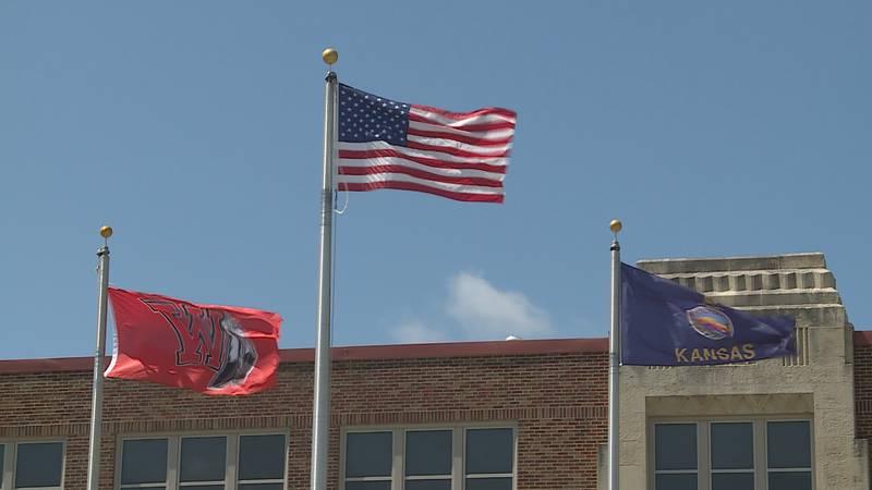 A Wamego, American and Kansas state flag waving outside Wamego High School.