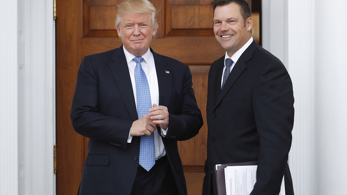 FILE - In this Nov. 20, 2016, file photo, Kansas Secretary of State Kris Kobach, right, holds a...
