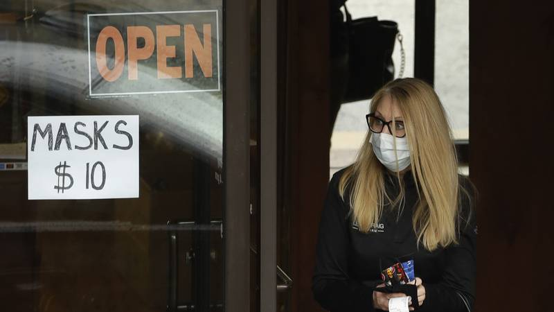 FILE - A woman leaves a shop after purchasing face masks Thursday, May 7, 2020, in Kansas City,...