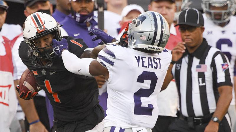 Kansas State defensive back Russ Yeast (2) grabs the face mask of Oklahoma State wide receiver...