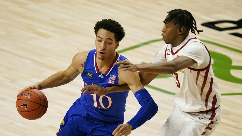Kansas forward Jalen Wilson (10) drives past Iowa State forward Javan Johnson, right, during...
