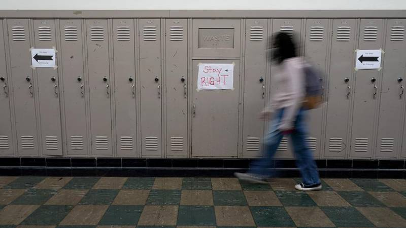FILE - A student walks between classes at Wyandotte High School in Kansas City, Kan., on the...