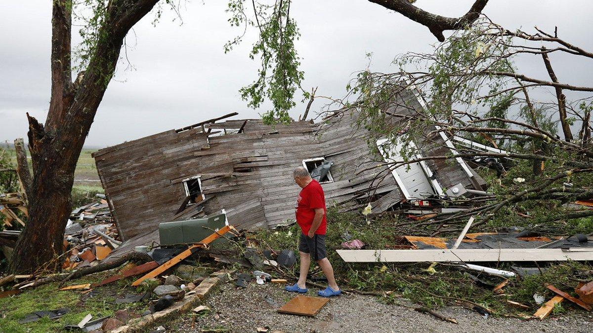 Joe Armison looks over his destroyed barn after a tornado struck the outskirts of Eudora, Kan.,...