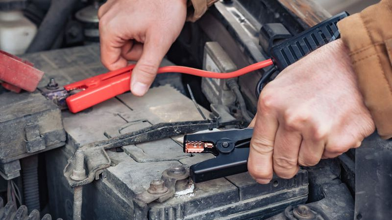 Man recharging a dead car battery in winter time using start-charger. Close up hands of a man...