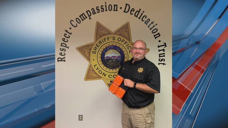 Lyon County Sheriff, Jeff Cope, accepts a donated flare kit set from AAA Kansas.