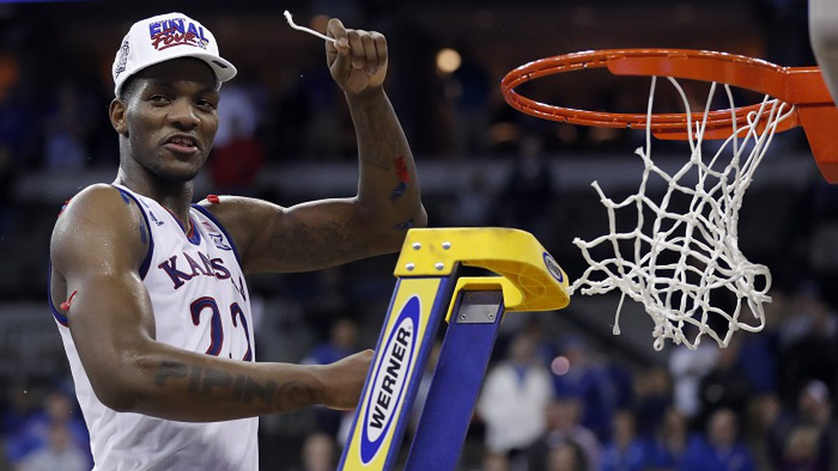 Kansas' Silvio De Sousa celebrates by cutting down the net after defeating Duke in a regional...