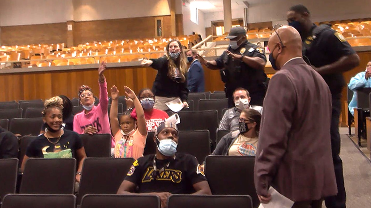 FILE - People in the JCPS school board meeting crowd disrupted Tuesday's meeting over armed...
