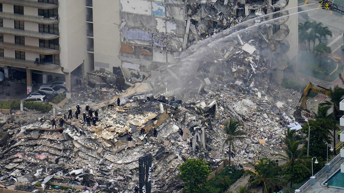 FILE - Rescue workers work in the rubble at the Champlain Towers South Condo in Surfside, Fla.,...
