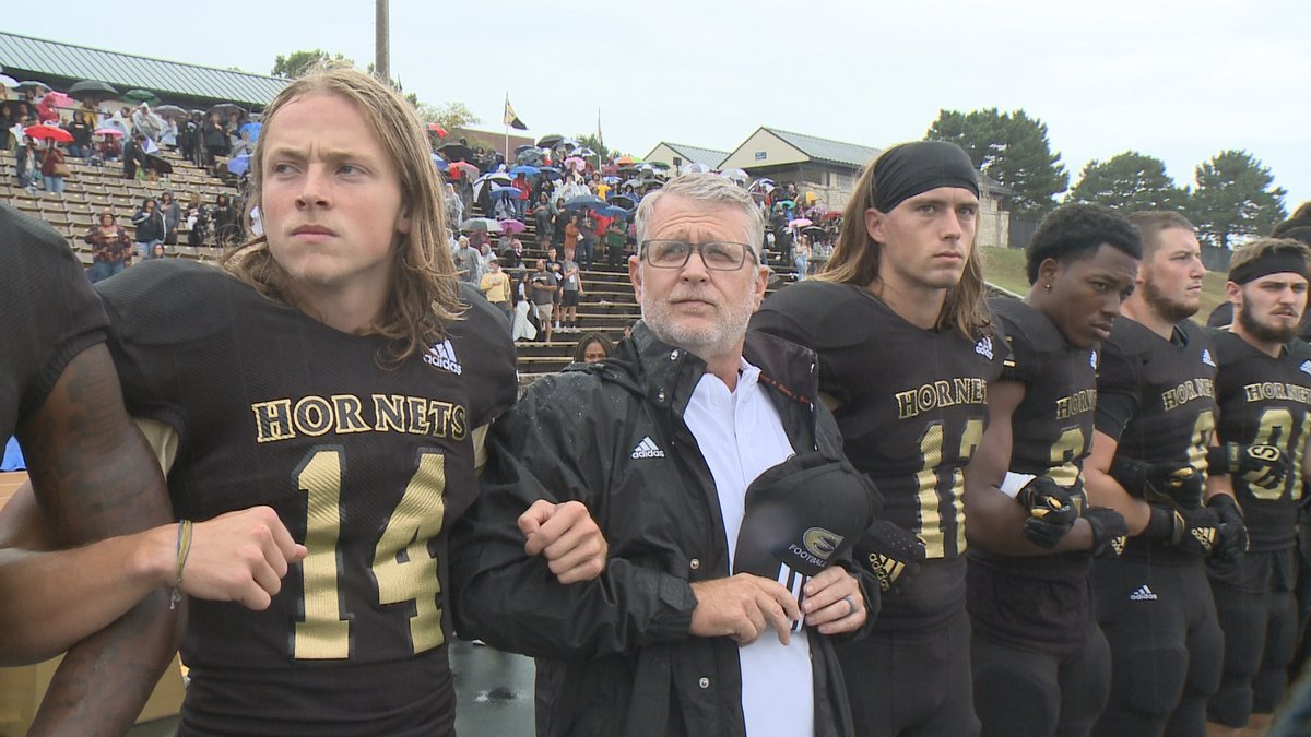 Emporia State head football coach Garin Higgins stands arm-in-arm with several football players...