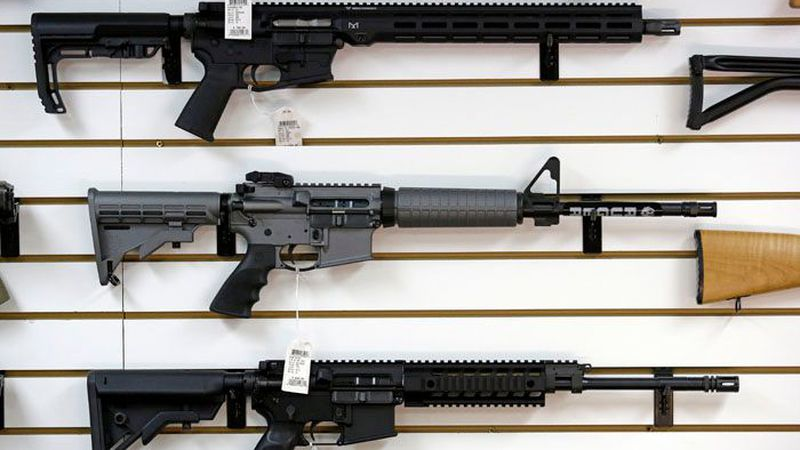 FILE - A Ruger AR-15 semi-automatic rifle, center, sits on display with other rifles on a wall...