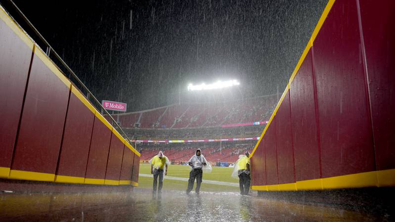 Security guards stand off the field at Arrowhead Stadium as a steady rain falls during halftime...