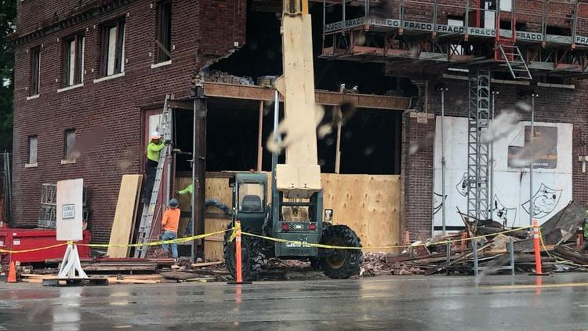 Construction workers cover a whole left by a vehicle after an early morning hit and run at the...