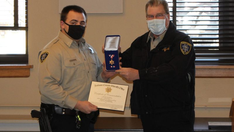 Jackson County sheriff's Deputy Chad Ballenger, left, receives an award from Sheriff Tim Morse...