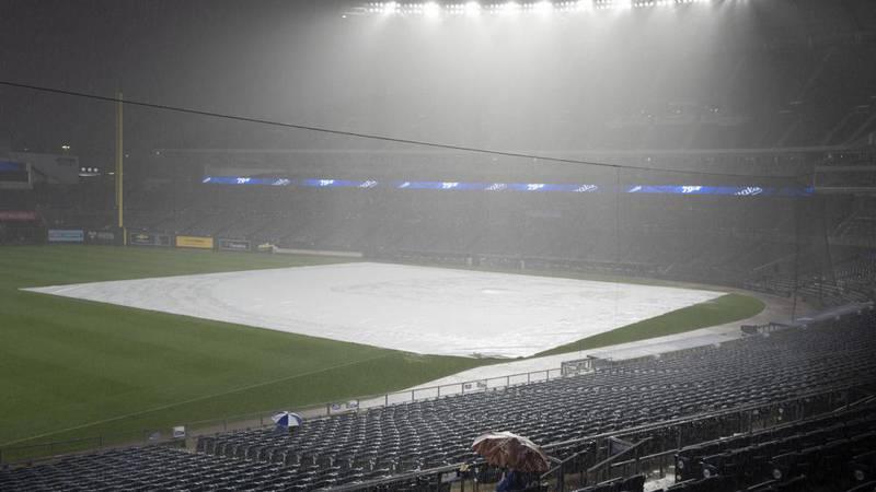 A few fans sit through a deluge at Kauffman Stadium that forced a rain delay in a baseball game...