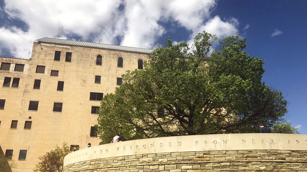 """Visitors to the Oklahoma City National Memorial walk around the """"Survivor Tree,"""" a 100-year-old..."""
