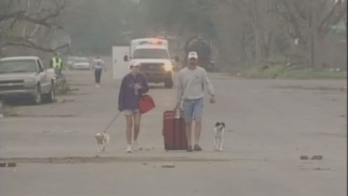 A couple walks down a Greensburg street after an EF5 tornado levels most of the town.