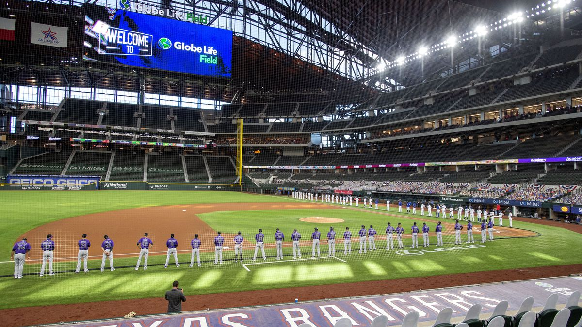 The Texas Rangers and Colorado Rockies line the foul lines of Globe Life Field before an...